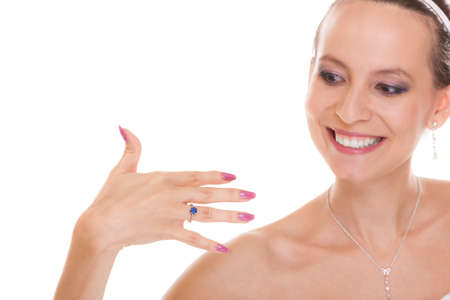 admiring: Joyful happy bride admiring engagement ring on finger. Excited woman in white wedding dress isolated on white background. Stock Photo