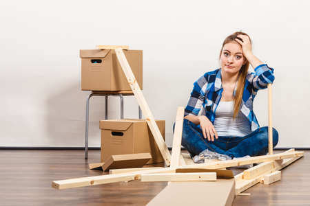 Worried woman moving into new apartment house assembling furniture. Young girl arranging interior and unpacking boxes.