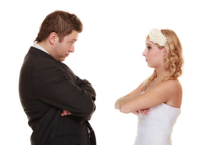 sullenly: Wedding couple conflict, bad relationships. Woman bride and man groom crossed arms looking at each other with angry expression. Isolated on white Stock Photo