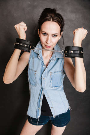 Arrest and jail. Criminal woman prisoner girl showing leather handcuffs on gray. Punishment.