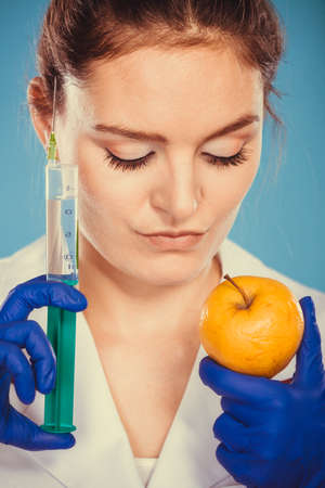 modified: Scientist doctor with apple and syringe. Woman chemist holding genetically modified fruit. GM food modification.