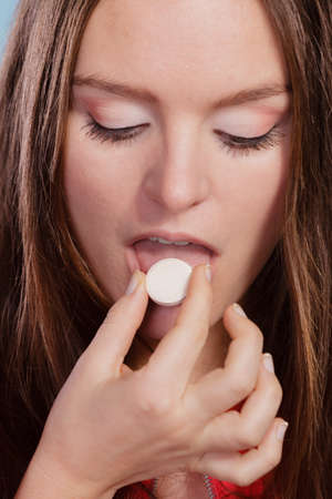 swallowing: Woman girl taking swallowing painkiller pill tablet. Health care. Headache and pain. Stock Photo
