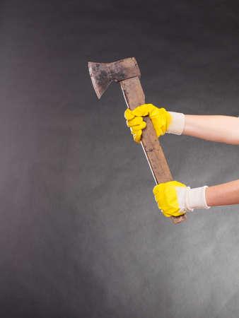 hatchet: Closeup human hands wearing safety work gloves holding axe chopper hatchet. Work.