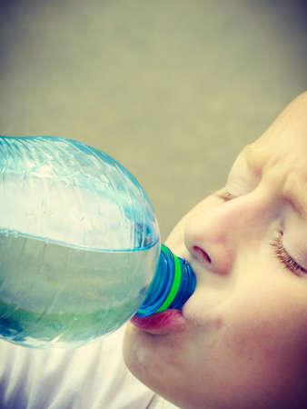 sediento: Poco sediento bebida ni�o ni�o de la botella pl�stica, al aire libre
