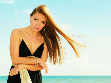 long hair: Holidays, summertime travel and freedom concept. Portrait of lovely girl beauty healthy fluttering long hair outdoor. Young pretty tanned woman in summer clothing on sky background