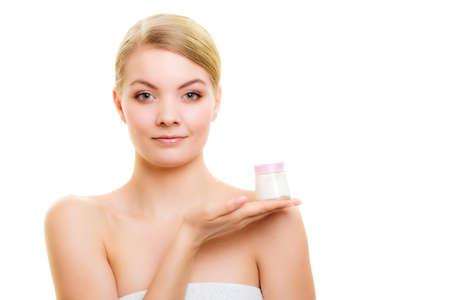 cosmeticos: Cuidado para la piel. Mujer joven que sostiene el tarro loción cosmética. Chica rubia que toma cuidado de su cutis seco aplicar aislado crema hidratante. Tratamiento de belleza.