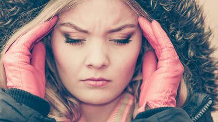 gripe: Retrato de la mujer bastante de moda que sufren de dolor de cabeza. Chica joven en la chaqueta con capucha llam� virus de la gripe fr�o. La ca�da del oto�o de la moda de invierno. Filtro de Instagram. Foto de archivo