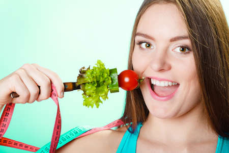 loss weight: Dieting weight loss concept. Sporty girl fitness woman holding fork with fresh mixed vegetables and measuring tape on blue background. Stock Photo