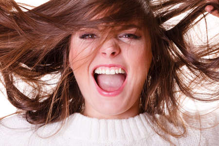 Shouting happy crazy girl with hair acting insane.