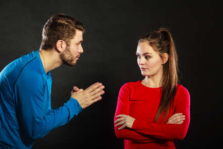 relationship problems: Husband apologizing upset angry wife. Man asking woman for forgivness. Boyfriend trying to convince girlfriend. Conflicted couple in studio on black. Relationship problem.