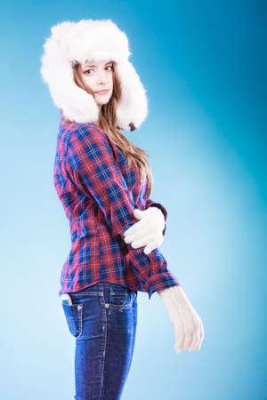 white fur: Winter fashion. Close up young woman wearing fashionable wintertime clothes white fur cap studio shot on blue background Foto de archivo