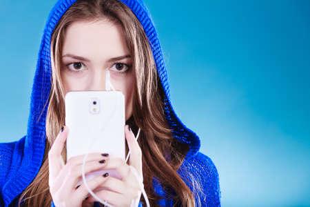 adolescente: mujer joven con música que escucha inteligente teléfono. Niña de pelo largo adolescente con estilo en el capó lenguaje de relax o de aprendizaje. Estudio tirado en azul vivo. Foto de archivo