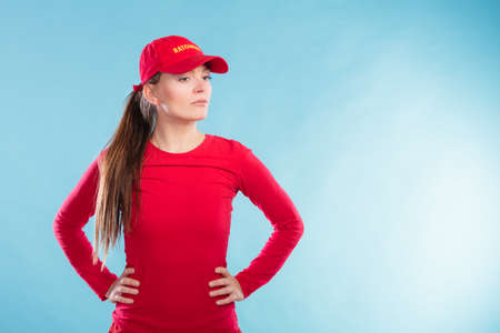 Portrait of lifeguard woman girl in red cap with ratownik sign on blue. Accident prevention rescue. Stock Photo