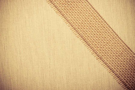 bagging: Jute bagging ribbon on bright fabric textile material, natural linen background