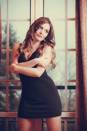 chica sexy: Retrato de la hermosa mujer sexy por la ventana de la puerta francés en casa. Atractiva chica sensual joven con el pelo largo en la ropa interior. La moda femenina. Filtro de Instagram.