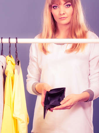 spend: Pretty woman with empty wallet want clothing from wardrobe. Young undecided shopper girl spend all money for clothes. Shopaholic concept. Stock Photo