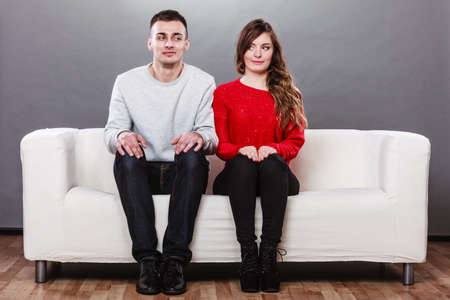 Shy woman and man sitting on sofa couch next each other. First date. Attractive girl and handsome guy meeting dating and trying to talk. Banco de Imagens