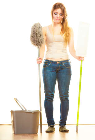 mops: Cleanup housework concept. Tired cleaning lady young woman mopping floor, holding two mops new and old white background