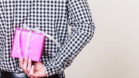Man hiding pink gift box with white ribbon behind back. Closeup of male hand holding christmas present. Guy wearing flannel shirt. Birthday, holiday surprise.
