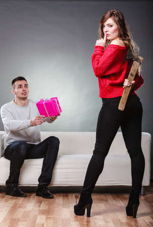 insincerity: False feelings, relations problem. Trusting guy giving present pink box to misleading girl. Insincere woman holding axe behind her back Stock Photo