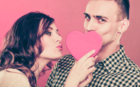 closeness: Young happy loving couple kissing behind red heart - sign symbol of love. Relationship closeness. Stock Photo