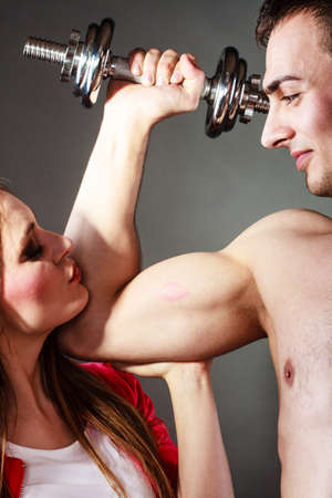 lustful: Bodybuilding. Strong man exercising with dumbbells. Closeup muscular guy flexing lifting weights, girl looking admiringly kissing his biceps. Stock Photo