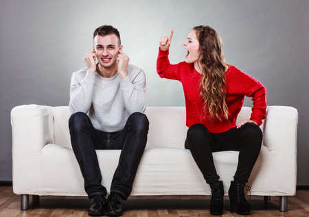 bother: couple having argument - conflict, bad relationships. Angry fury woman screaming man closing his ears.