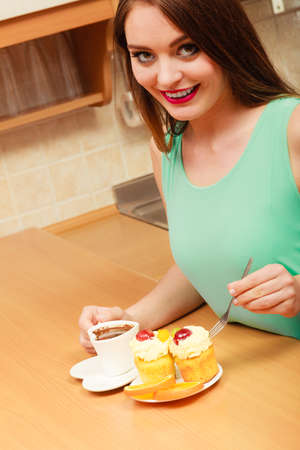 gula: Woman with cup of coffee forking delicious gourmet sweet cream cake cupcake and orange. Glutton girl sitting in kitchen with hot beverage having breakfast. Appetite and gluttony concept. Foto de archivo
