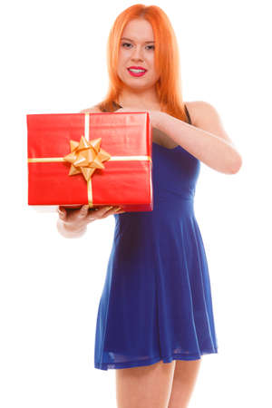 red head girl: People celebrating holidays, love and happiness concept - smiling red head girl in blue dress holds red gift box studio shot isolated. Time gifts Stock Photo