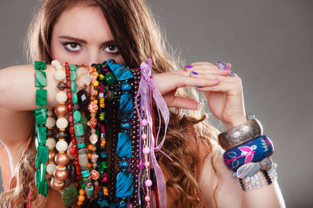 gorgeous woman: Pretty young woman wearing bracelets holding many plentiful of precious jewelry necklaces beads. Gorgeous fashion girl.
