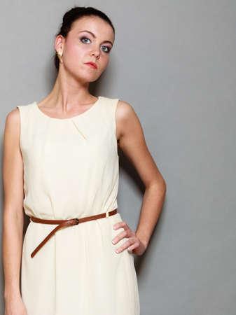 hait: Glamour girl in white dress on gray. Fashion young woman hait bun posing. Studio photo