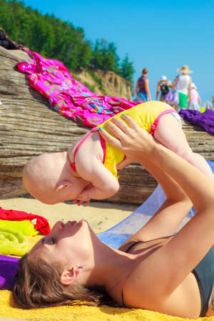 babyhood: Sweet little baby in mother parent hands. Babyhood and parenting. Summer vacation on beach. Stock Photo