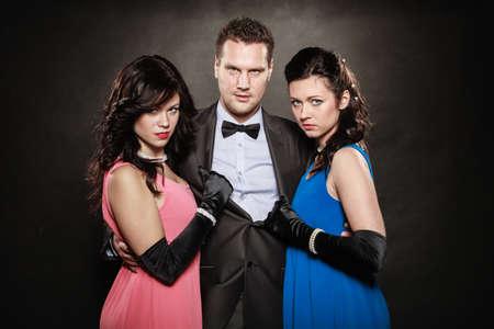 herrin: Dreiecksbeziehung. Portrait von zwei Frauen und ein Mann tragen elegante Kleidung auf schwarz. Herrin und Verrat innerhalb der Familie. Wahl vor der Hochzeit. Luxus-Party.