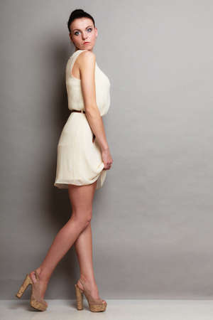 glamour girl: Glamour girl in white dress on gray. Fashion young slim woman posing in full length. Studio photo Stock Photo