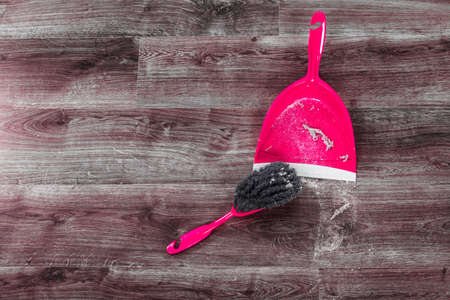 brooming: Cleaning and home concept. Sweeping brush small whisk broom and dustpan for house work with garbage on floor indoors.