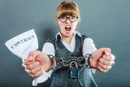 office slave: Business and stress concept. Furious businesswoman in glasses with chained hands holding contract grunge background Stock Photo