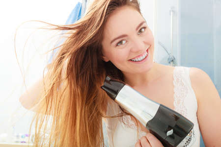 secador de pelo: Cuidado del cabello. Hermoso pelo largo cabello seco de la mujer en el baño