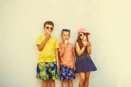 Niños comiendo helado y suave servir helado. Los niños y niña en gafas de sol disfrutando de las vacaciones de verano vacaciones. Filtro de Instagram. Foto de archivo - 47782260