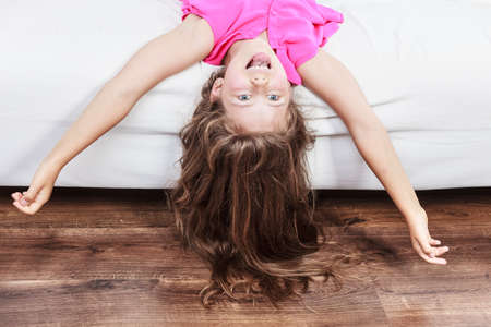 girl lying down: Happy little girl with long hair lying upside down on sofa at home. Kid playing having fun on couch.