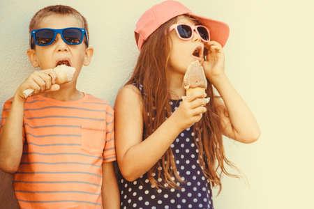 gelato 및 소프트 먹는 아이 아이스크림을 제공합니다. 소년과 여름 방학 휴가를 즐기는 선글라스에 어린 소녀. Instagram 필터.