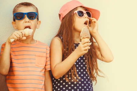 Kids eating gelato and soft serve ice cream. Boy and little girl in sunglasses enjoying summer holidays vacation. Instagram filter. Stock Photo