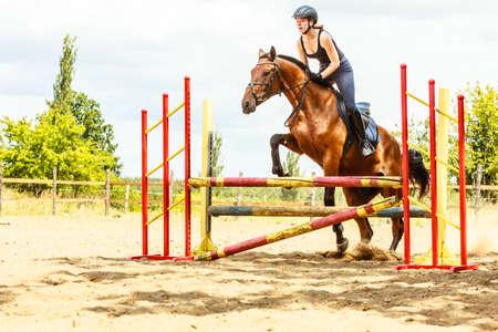 salto de valla: Mujer activa chica entrenamiento jinete equitaci�n saltar sobre la cerca. Competici�n deporte ecuestre y actividad.