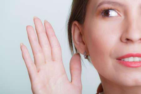 oreja: El chisme espionaje chica con la mano al oído. Mujer oír escuchar rumores. Espionaje y el concepto de secreto.