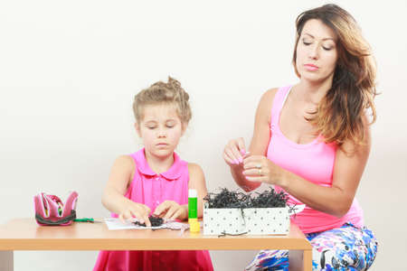 mothering: Little girl work with mom. Parenting, cooperation, common fun