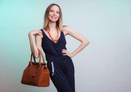 leather: Elegant fashionable woman with leather handbag. Stylish girl on green holding brown bag. Women fashion vogue. Studio.