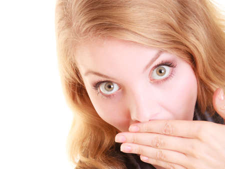 Surprised embarrassed woman face, girl covering her mouth with hands over white background Stock Photo