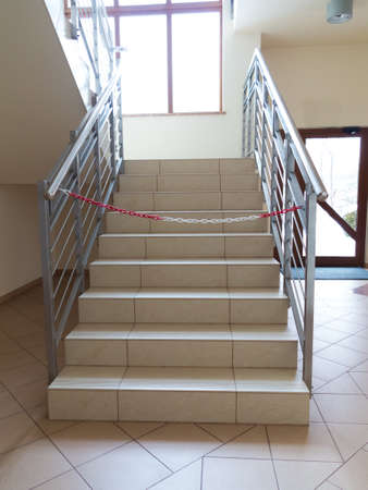no entrance: Interior empty stairway with tiled floor. Entrance stairs closed with rope, no entry sign.