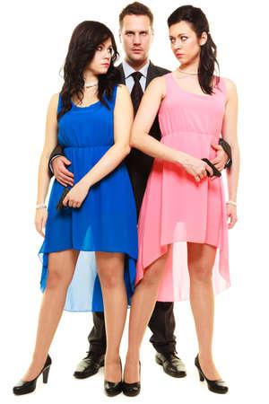 celos: Los celos entre las mujeres en relación triángulo. Dos elegantes mujeres con armas de fuego y el hombre en traje de aislados en blanco. Estudio de disparo.