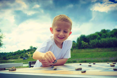 board game: Draughts board game. Little boy clever child kid playing checkers thinking outdoor in the park. Childhood and development