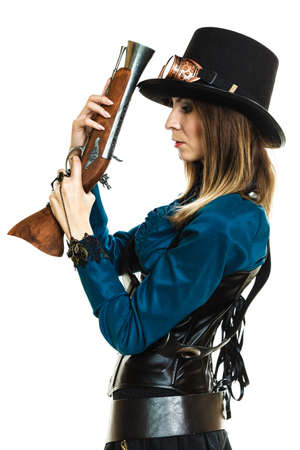 finger on trigger: Young steampunk islolated girl on white holding fancy rifle with finger touching trigger. Fantasy old fashion wearing hat and goggle.